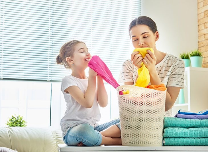 Beautiful young woman and child girl little helper are smelling clean clothes and smiling while doing laundry at home