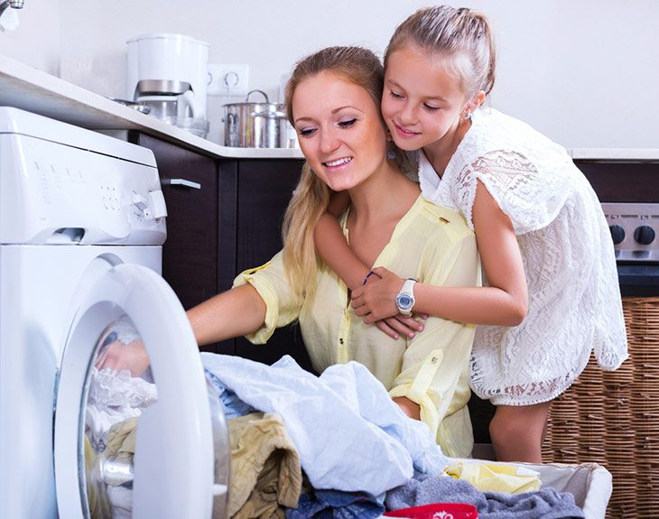 housewife and little girl doing laundry together